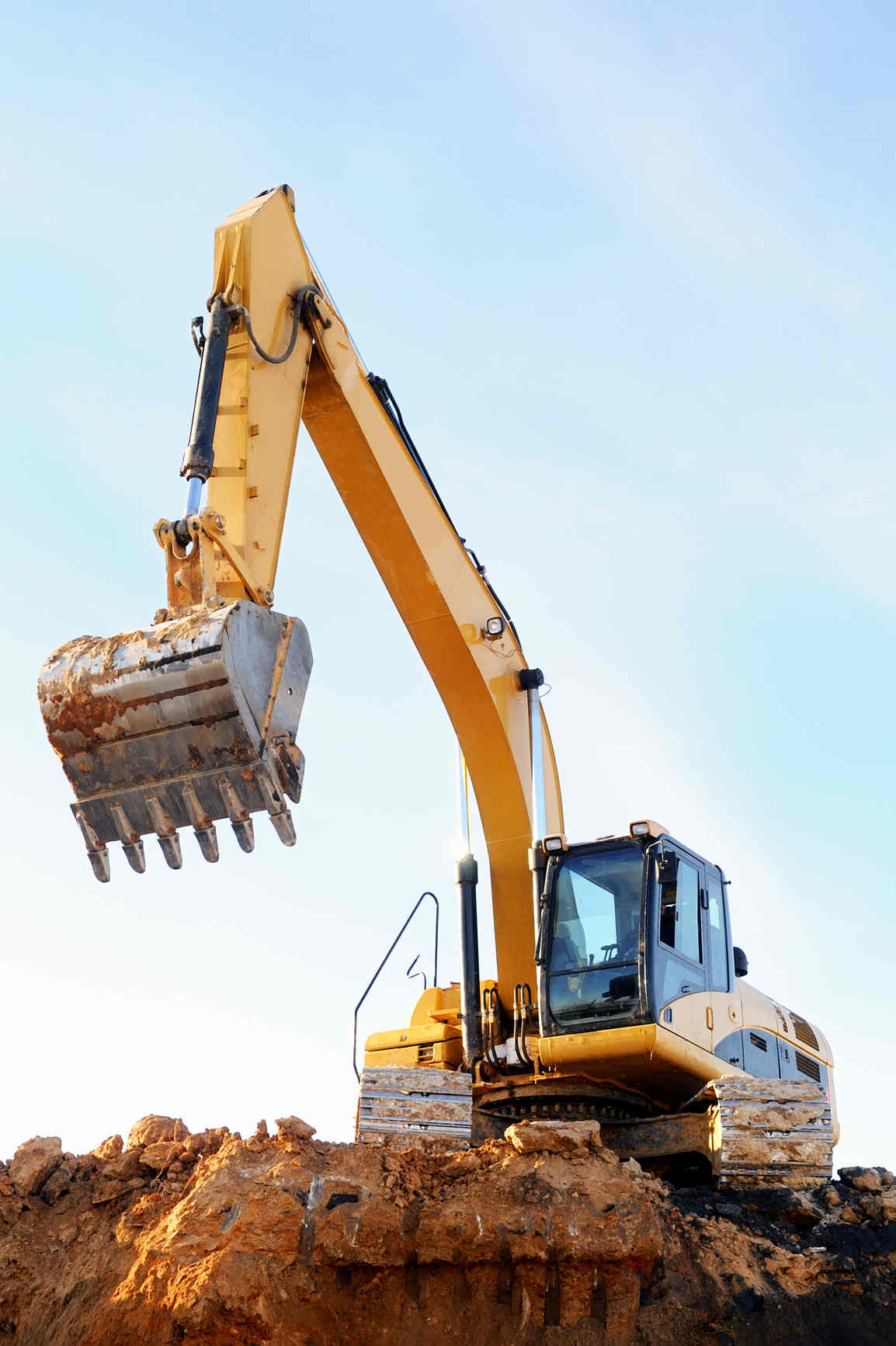 Image of an excavator on top of a dirt mound