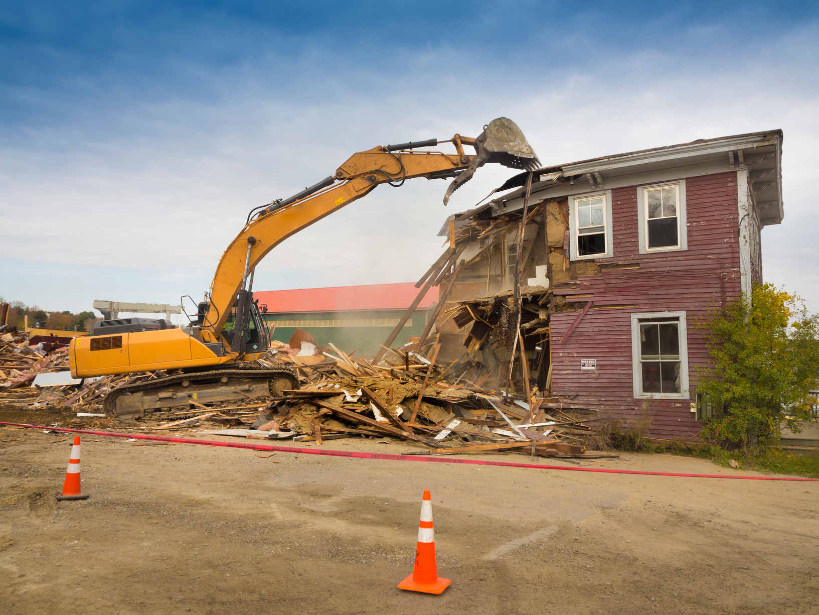 Excavator demolishing an old red wooden building